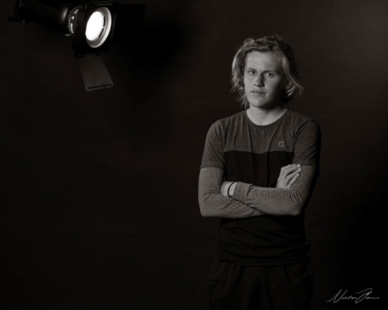 Black and white portrait of Sydney student and actor Michael Hawkins, standing with arms crossed over chest.