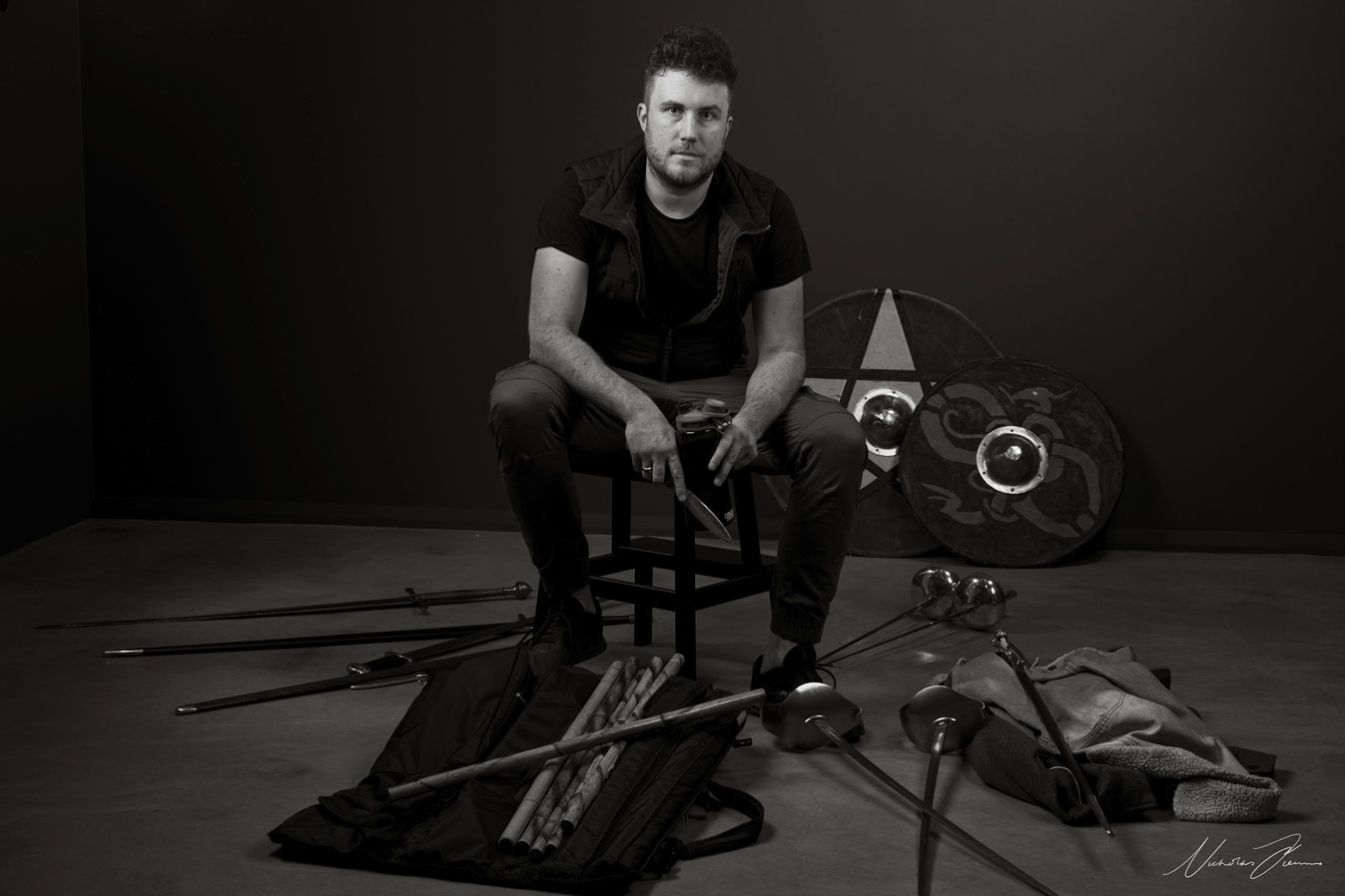 Tim Dashwood, Theatre Fight Director and Actor, surrounded by battle equipment