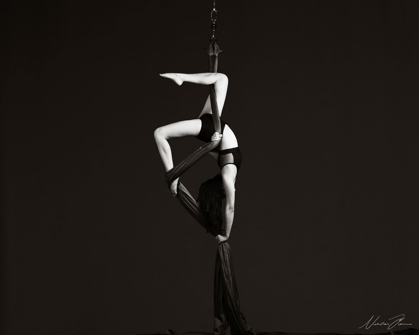 Amanda Lum, posing mid-air upside down using circus aerial silks