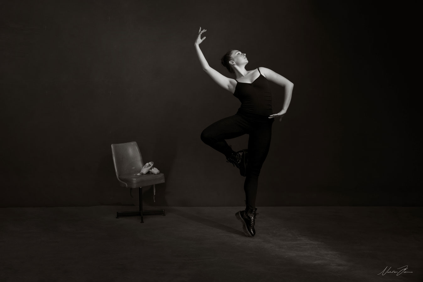 Black and white portrait of ballet and contemporary dancer Maeve Nolan, in a ballet pose wearing black tights and Dr Martins boots.