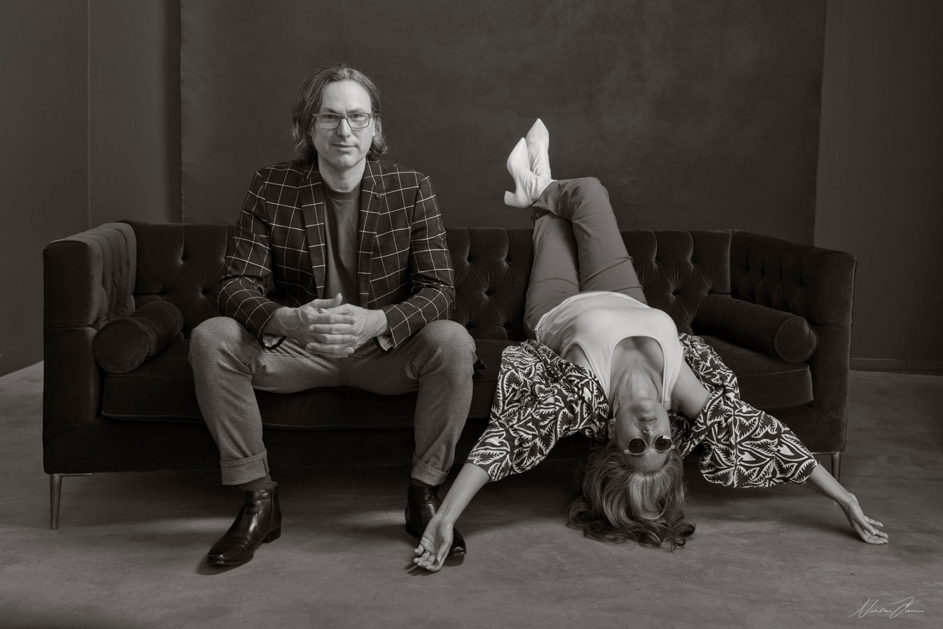 Black and white portrait of Sydney husband and wife duo Gavin and Niyati Libotte on a couch.