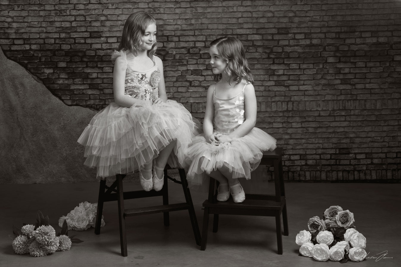 Black and white portrait of little ballerinas Lior and Noa, sitting on step stools.