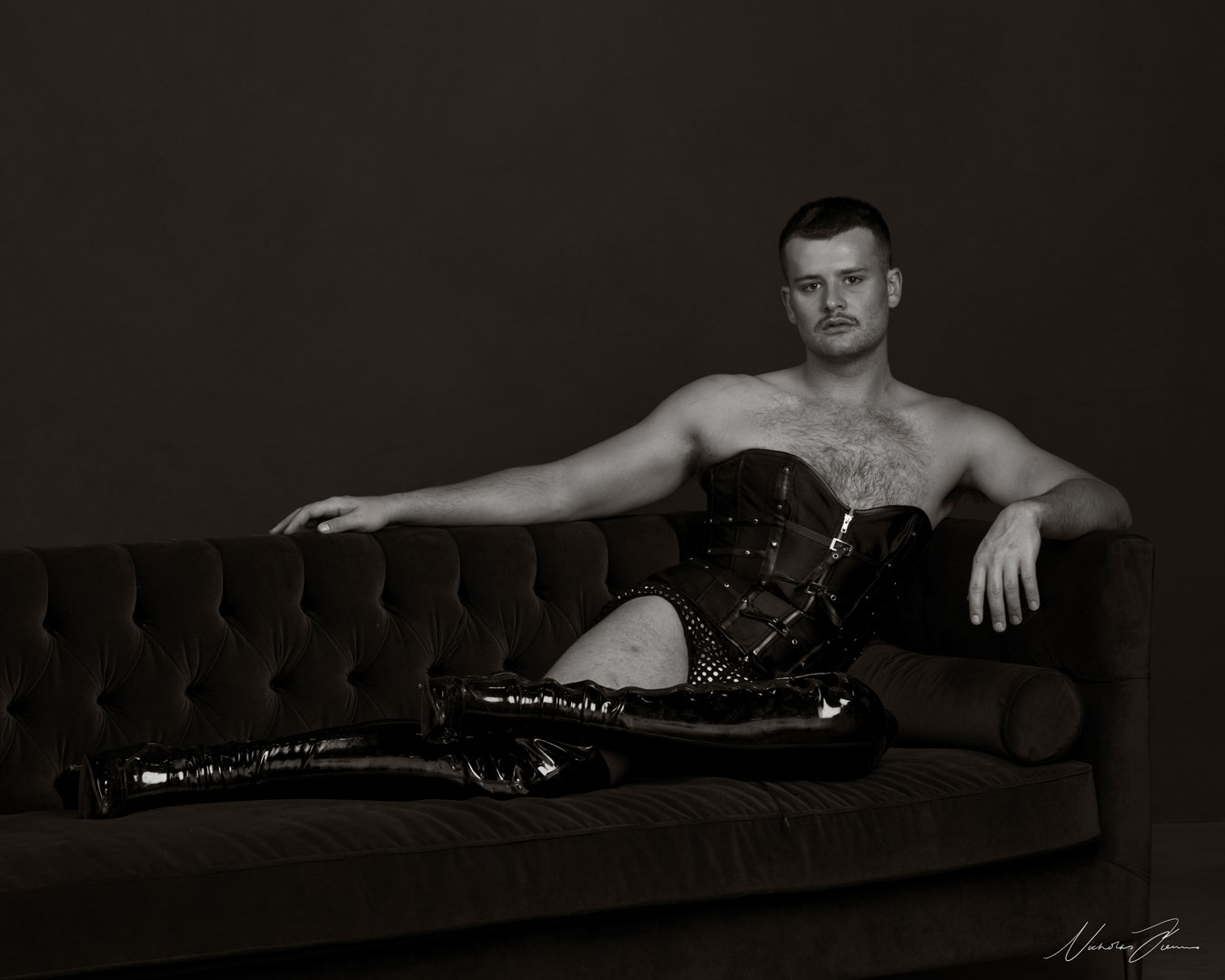 Black and white portrait of performer, writer, and theatre maker Tom Crotty, lounging on sofa wearing a corset and high boots.