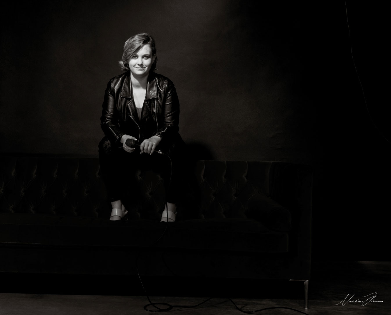 Black and white portrait of Sydney singer Jemma Charlin, perched on sofa holding microphone.