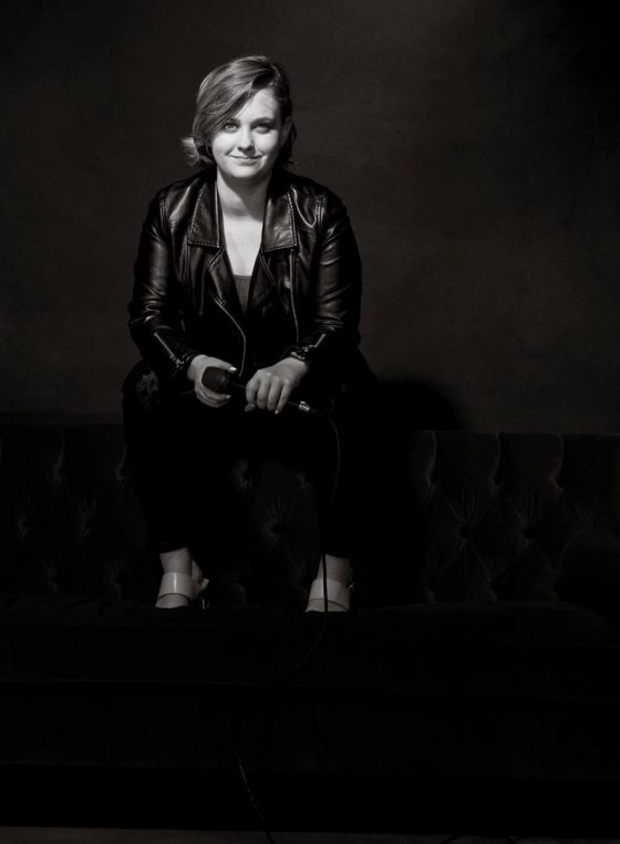Black and white portrait of Sydney singer Jemma Charlin perched on a lounge chair, holding a microphone.