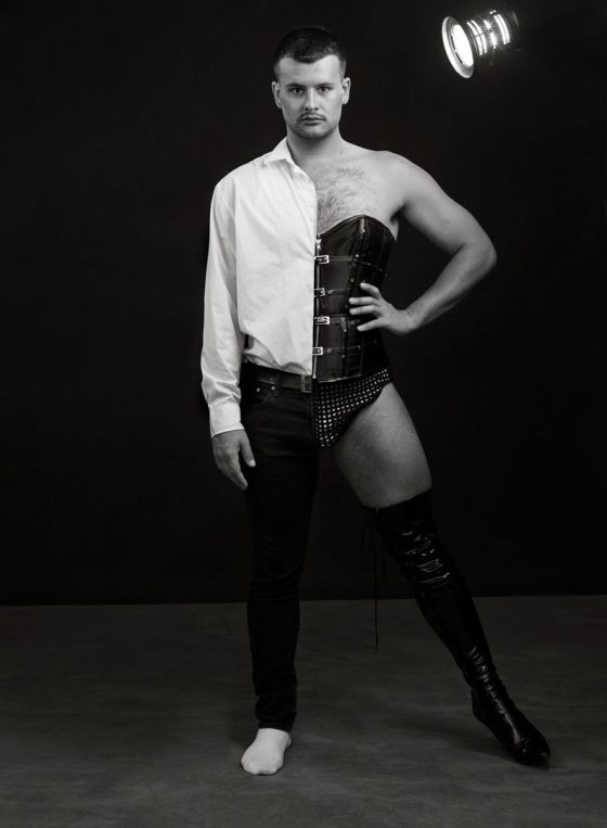 Black and white portrait of Sydney performer, writer, and theatre maker Tom Crotty, striking a pose wearing a half and half costume.