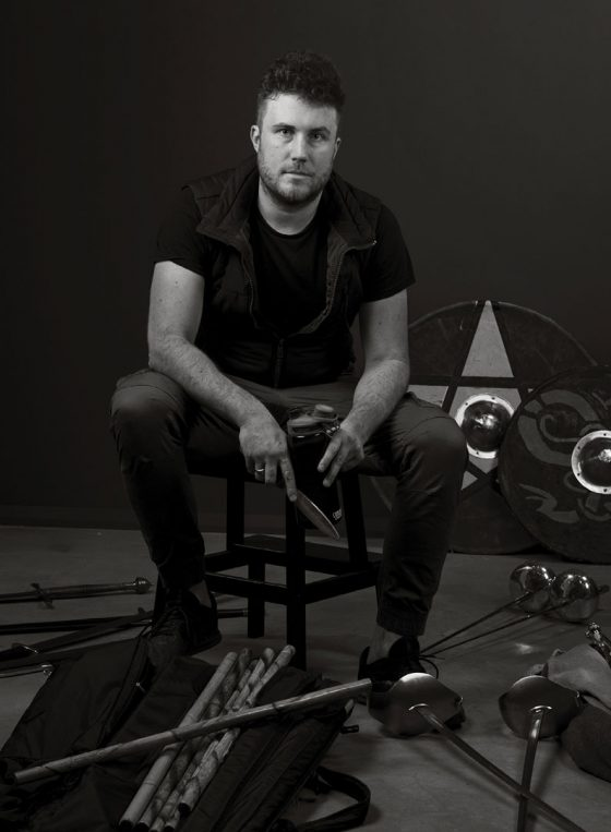 Black and white portrait of theatre fight director and actor Tim Dashood, sitting on stool, surrounded by theatre weapons.