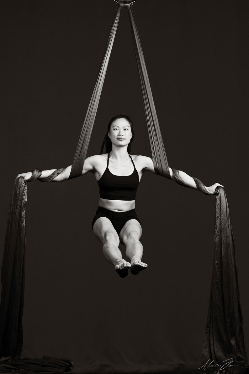 Black and white portrait of Sydney circus aerial silks dancer Katherine Huang, mid air supported by silks.