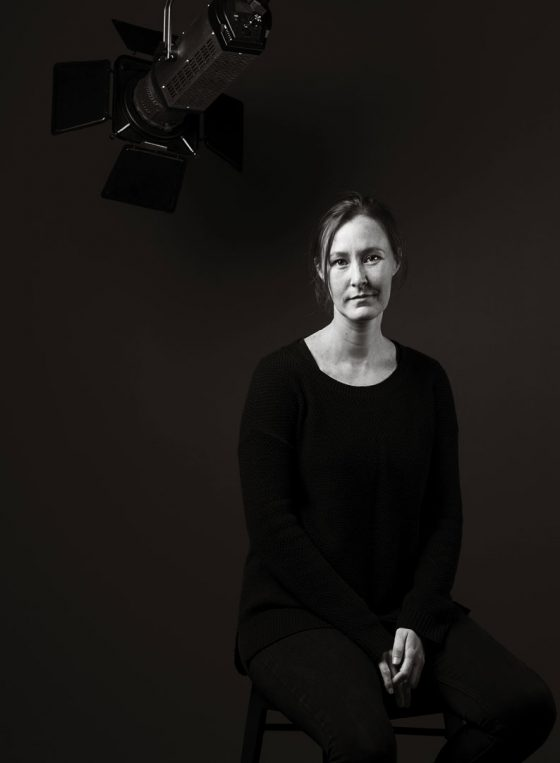 Black and white portrait of Sydney musical theatre stage manager Jessical Lawes, sitting on a step stool.