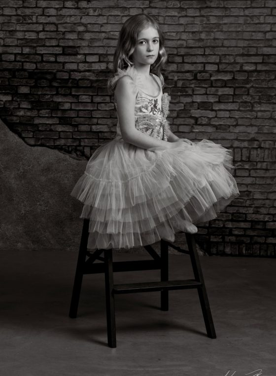 Black and white portrait of little ballerina Lior, sitting on a step stool.