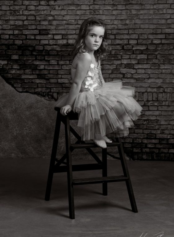 Black and white portrait of little ballerina Noa sits on a step stool.