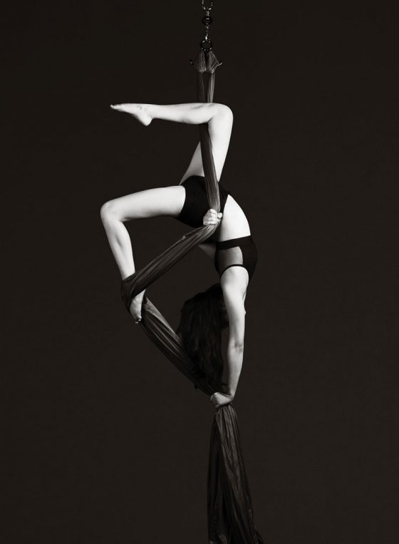 Black and white portrait of Sydney circus aerial silks dancer Amanda Lum, upside down mid air supported by silks.