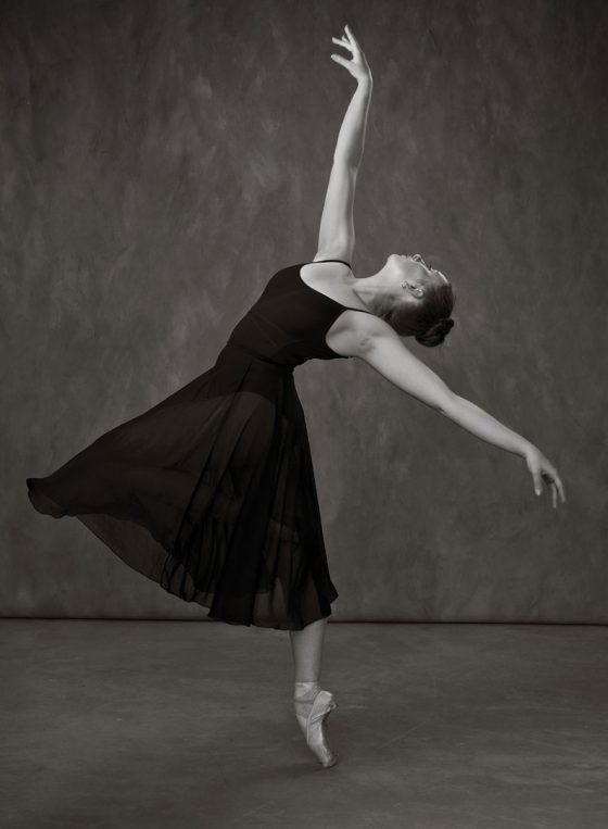 Black and white portrait of Sydney ballet and contemporary dancer Maeve Nolan, in a ballet pose.