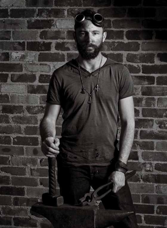 Black and white portrait of Sydney blacksmith Levi Pendlebury wearing googles and holding tongs and hammer resting on an anvil.
